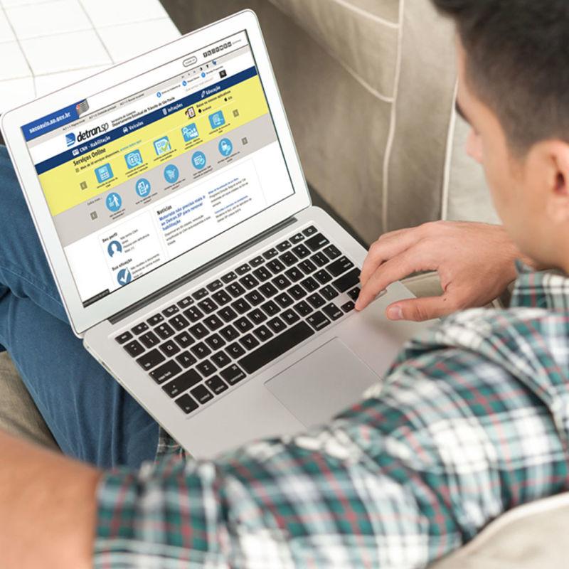 Homem com notebook aberto no site do Detran